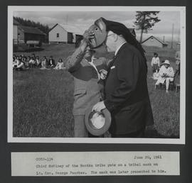 Chief McWiney of the Nootka tribe puts on a tribal mask on Lt. Gov. George Pearkes. The mask was ...